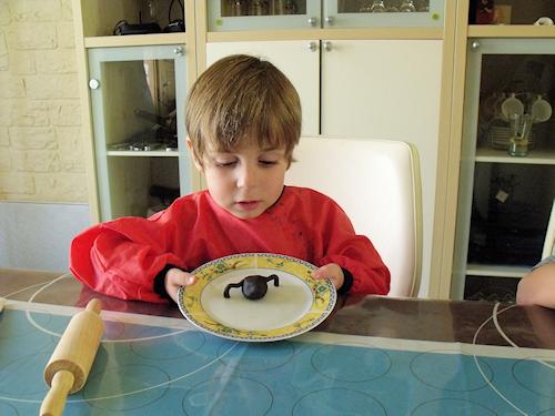 garçon fier de son araignée en pâte  d'amande pour décorer un gâteau d'Halloween