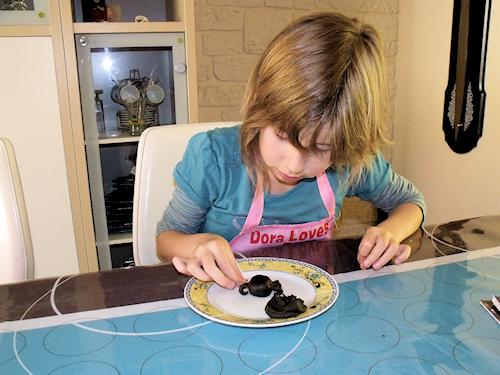 fille en train de faire du modelage en pâte d'amande pour décorer un gâteau d'Halloween