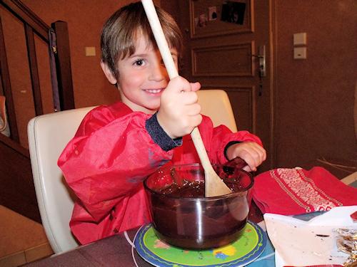 Enfant qui touille du chocolat fondu pour faire une recette au chocolat facile