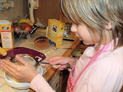 Enfant qui tamise de la farine pour faire un gateau au chocolat facile