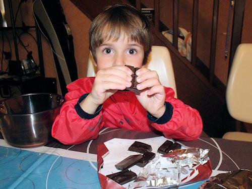 enfant qui coupe du chocolat pour une recette