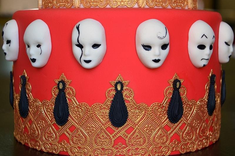 masques en pâte à sucre peints à la main sur l'étage rouge d'un gâteau carnaval