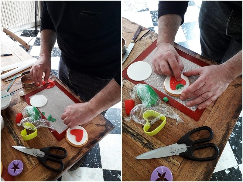 Dorian le blogueur en train de faire décorer des biscuits en pâte à sucre sur le thème de la fraise. Atelier pâte à sucre à domicile
